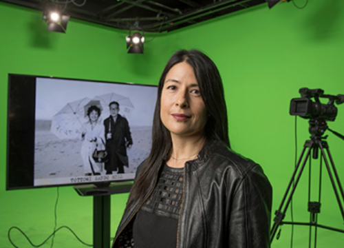 Pictured: Professor Takesue in front of a green screen.